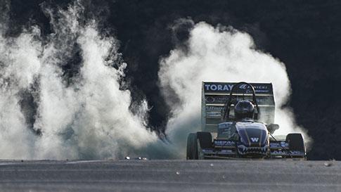 フォーミュラカーが車輪をスピンさせて煙を上げている画像