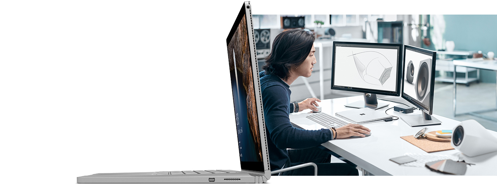 キーボード、マウス、2 つの外部ディスプレイに接続された Surface Book をデスクで作業する男性