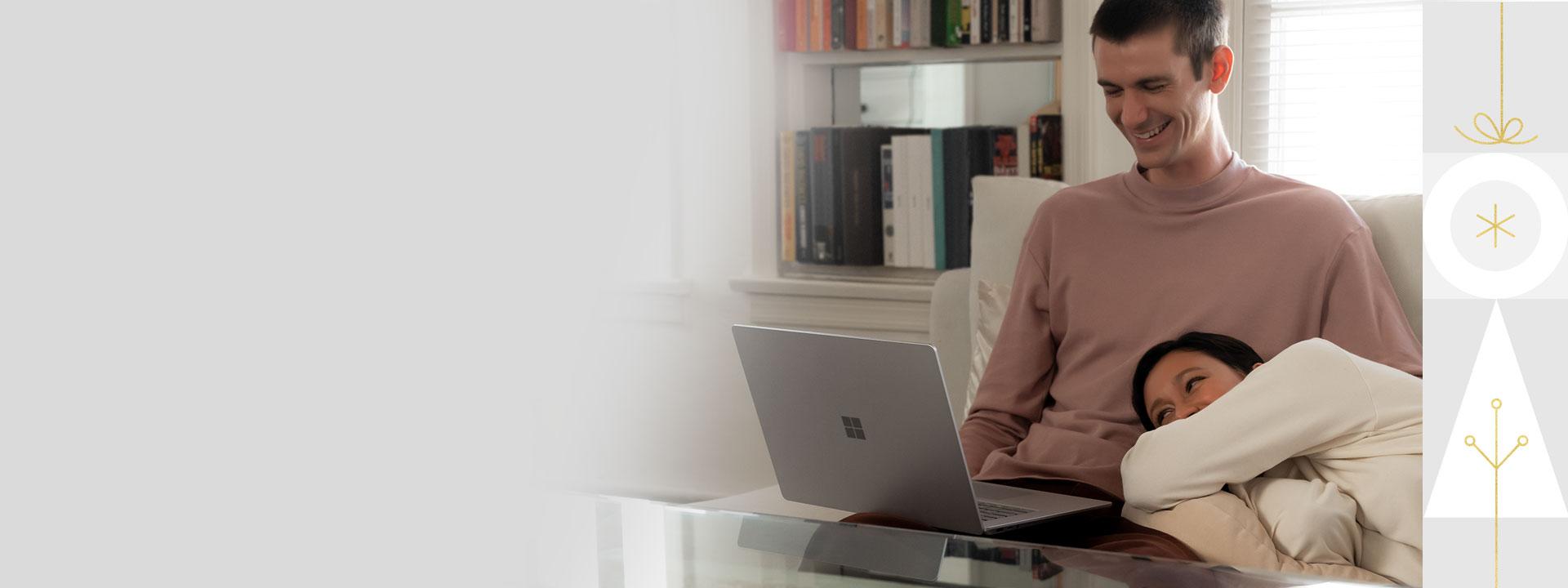 長椅子の上で Surface Laptop 3 を持っているカップル