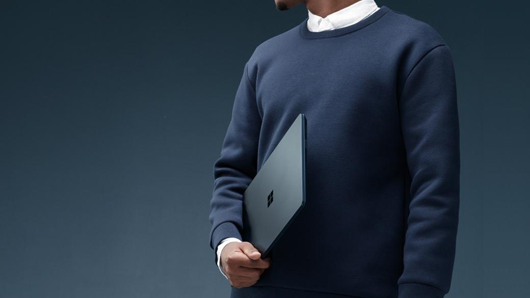 コバルト ブルーの Surface Laptop を右手に持っている男性。