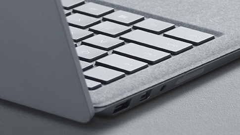ヒンジと Alcantara  キーボードを強調するプラチナの Surface Laptop の側面図。