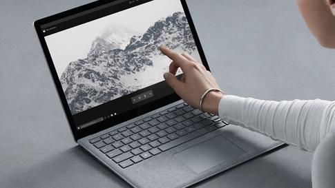 プラチナの Surface Laptop の画面に触れる女性。