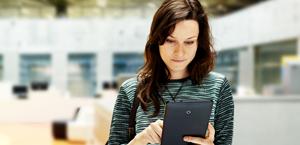 女性がタブレット コンピューターを見ています。Exchange Server 2019 の情報を参照します