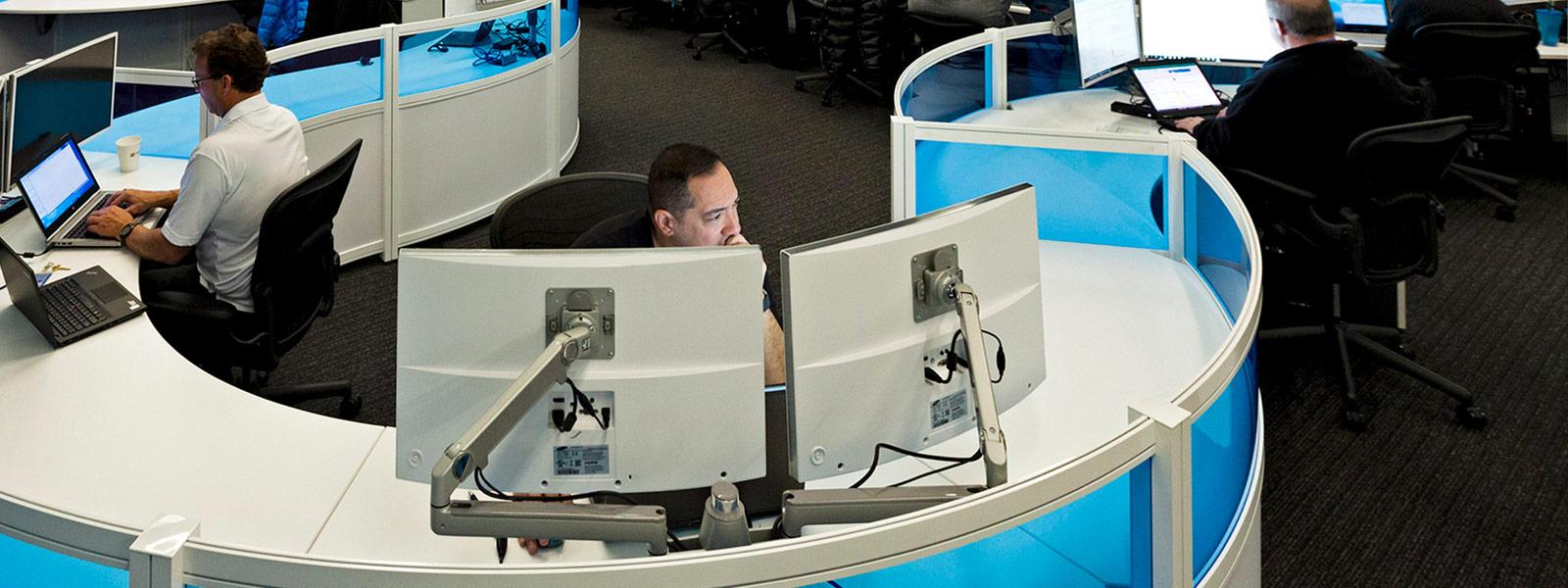 2 台のモニターをみているサイバー セキュリティ センターの男性