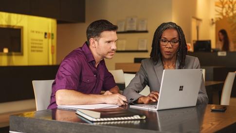 男性と女性がノート PC を持ってテーブルに座る