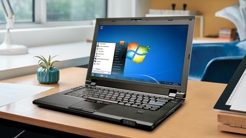 テーブルに置かれた、 Windows 7 を画面に表示しているノート PC