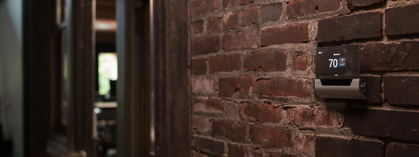 レンガの壁に取り付けられた温度調整パネル