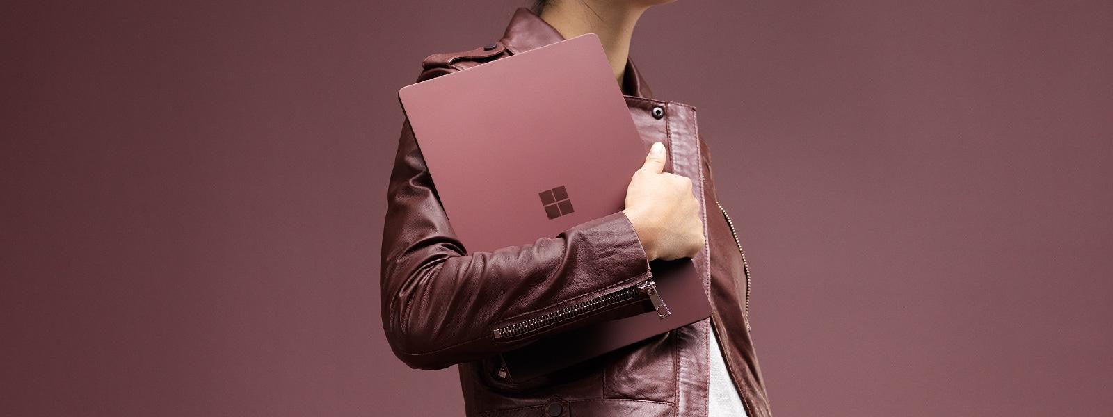 ワイン色の Surface Laptop を胸に抱えるファッショナブルな女性