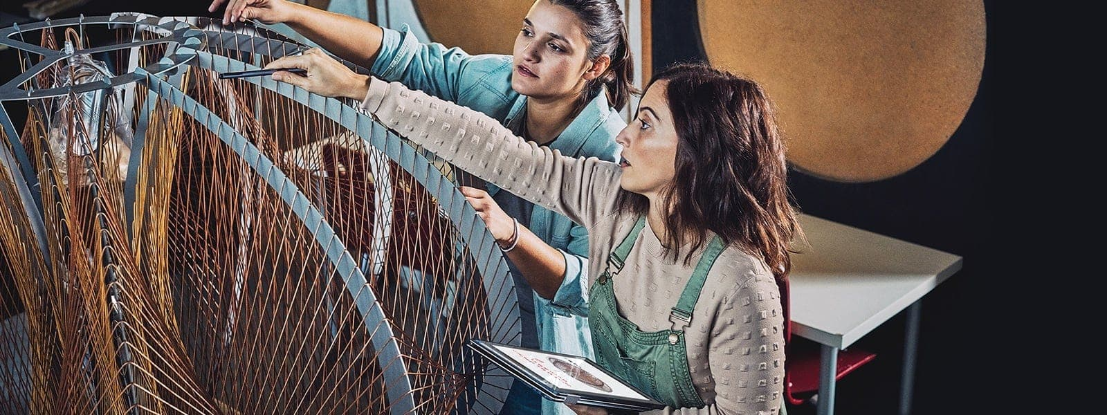 Dell デバイスを使用して、デジタル ベンで構造物をデザインする 2 人の女性