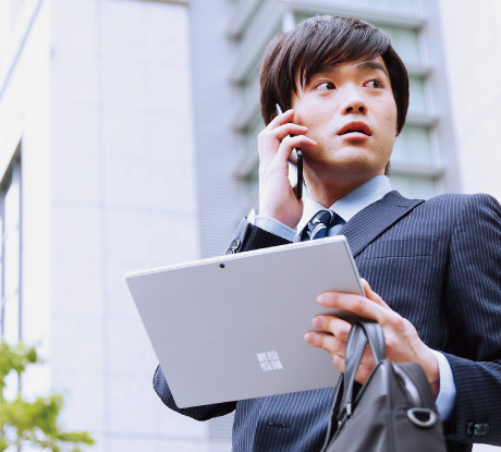 外出先で Surface Pro を片手に持ち、携帯電話で会話をする男性