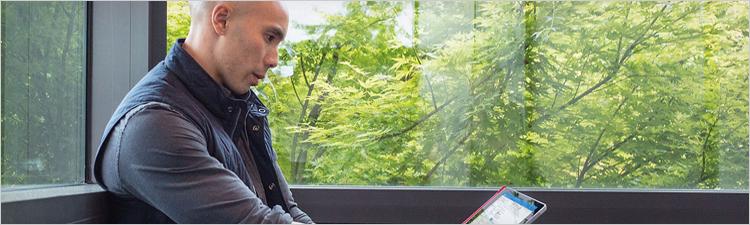 Планшеттік компьютерге қарап тұрған ер адам
