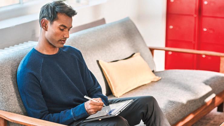 소파에 앉아서 디지털 펜을 사용해 Windows 10 컴퓨터를 조작 중인 남성