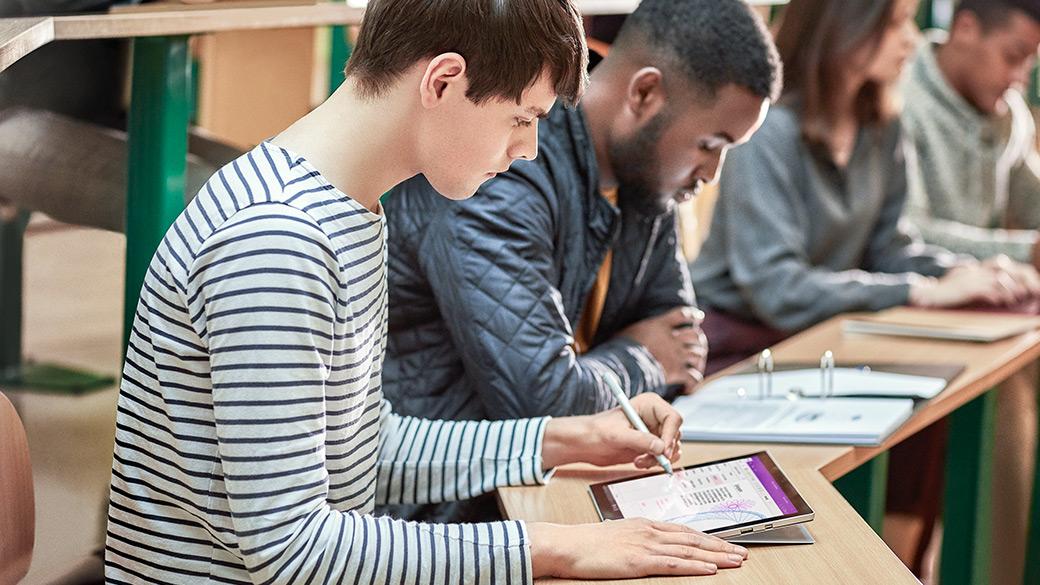 강당에서 주변의 다른 학생들이 자신의 노트를 바라보고 있는 가운데 태블릿 모드의 Surface Pro에 Surface 펜을 사용 중인 남학생