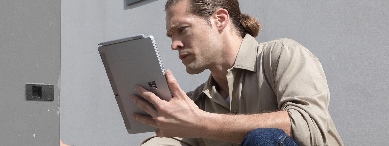현장에서 이동하며 태블릿 모드의 Surface Pro with LTE Advanced를 사용하는 남성 작업자