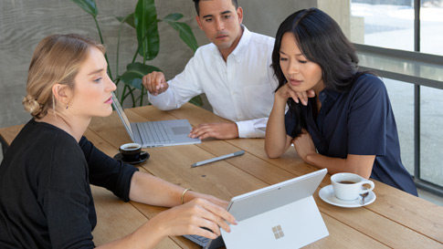 탁자에 앉아 Surface Pro 6(매트 블랙) 화면을 보면서 회의 중인 세 명의 동료