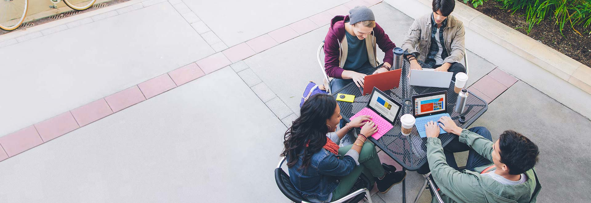 4명의 학생이 밖에서 테이블에 앉아 태블릿으로 교육용 Office 365를 사용하는 모습.