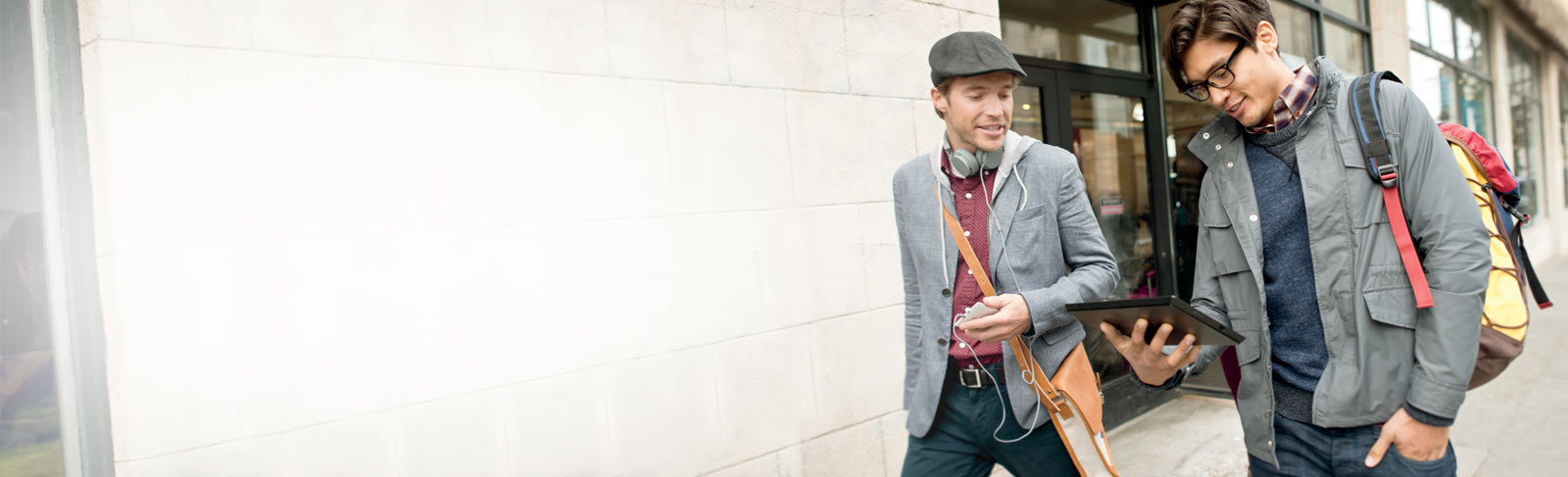 태블릿으로 Office 365를 사용하면서 길을 걷고 있는 두 남자