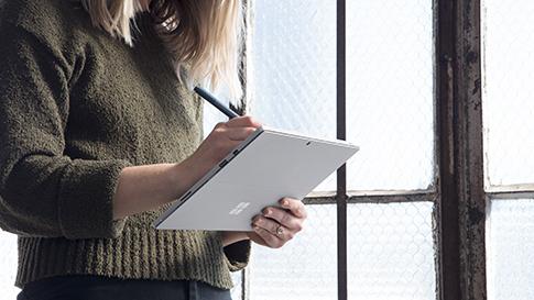 클립보드 모드의 Surface Pro에서 Surface 펜을 사용하는 여성.