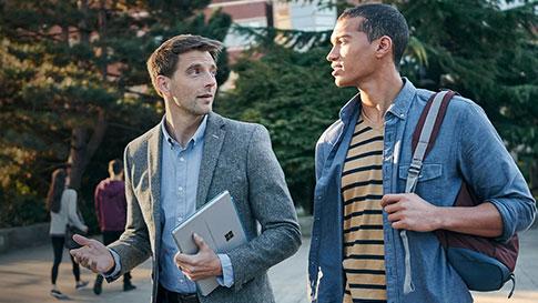 백팩을 들고 있는 남자와 Surface Pro 4를 들고 있는 남자가 함께 대화하며 걷고 있다.