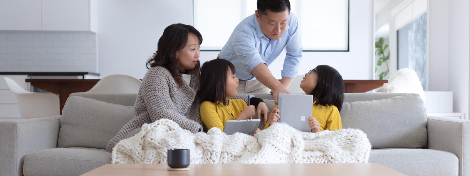 두 명의 아이가 두 개의 Surface Go 장치를 들고 소파에 앉아 있는 가족의 모습