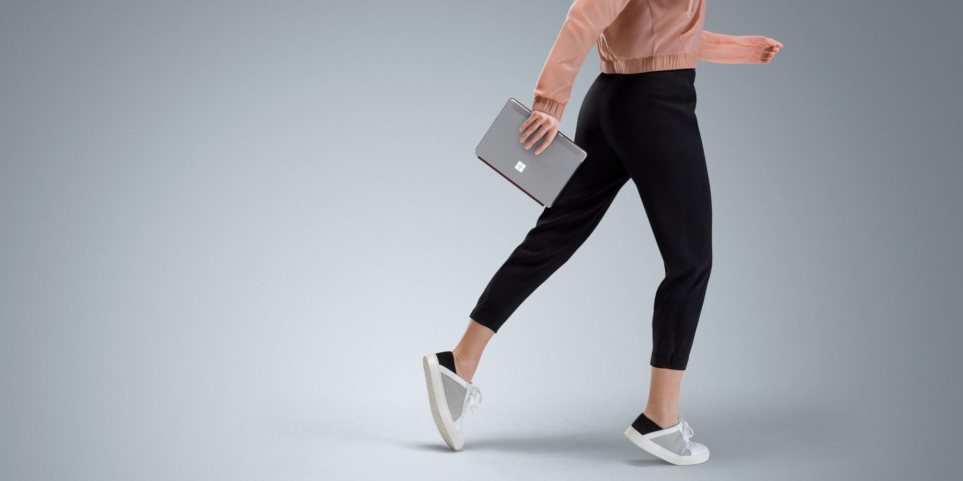 걷고 있는 여성의 손에 있는 Surface Go