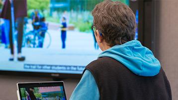 Žmogus su klausos aparatu žiūri vaizdo pristatymą su subtitrais