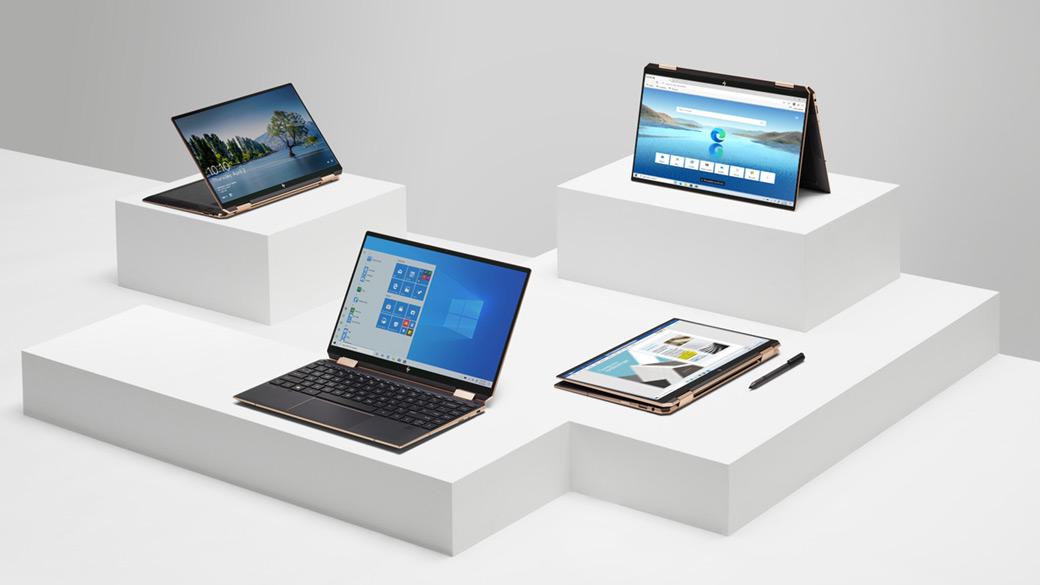 """Įvairūs """"Windows 10"""" nešiojamieji kompiuteriai, demonstruojami ant balto pjedestalo"""