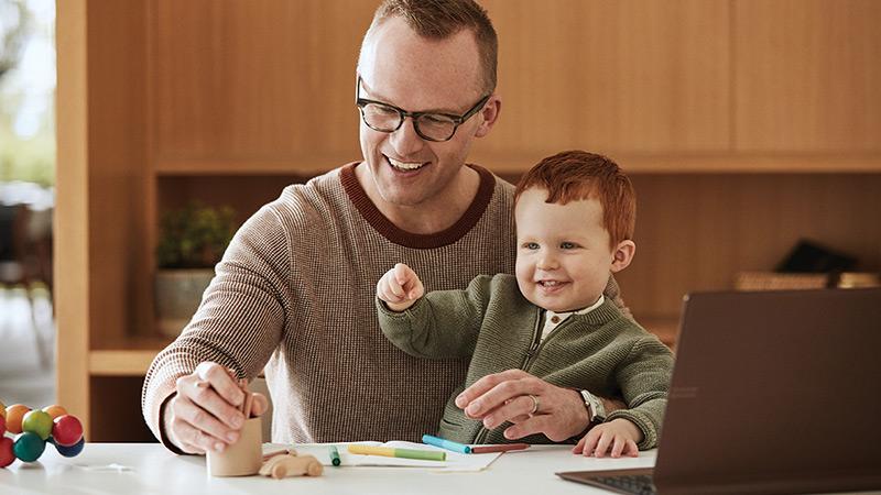 Vyras laiko ant kelių berniuką ir jie žaidžia su raštinės reikmenimis ir atidarytu nešiojamuoju kompiuteriu ant stalo