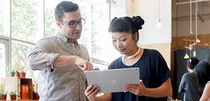 """Vyras ir moteris, dirbantys kartu planšetiniu kompiuteriu. Sužinokite apie """"Microsoft 365 Business"""" funkcijas ir įkainius"""