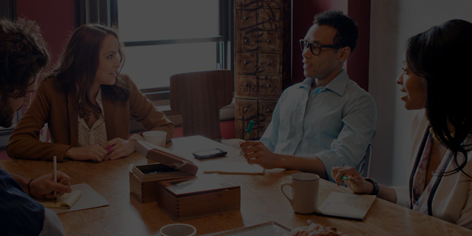 """Keturi žmonės, dirbantys biure ir naudojantys """"Office 365 Enterprise E3""""."""
