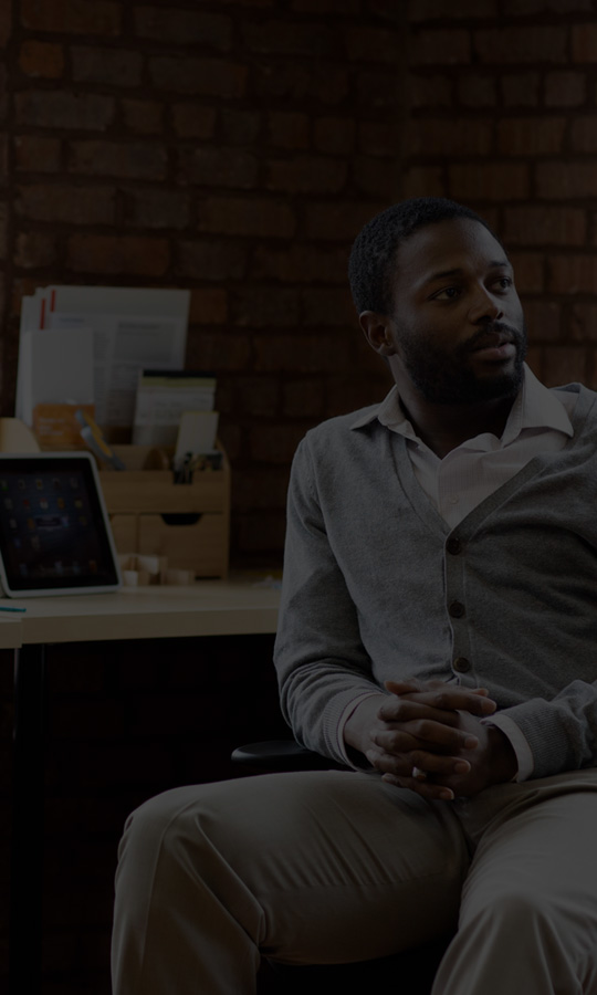 """Vyras sėdi prie stalo su planšetiniu ir nešiojamuoju kompiuteriu ir naudoja """"Office 365 Business Premium""""."""