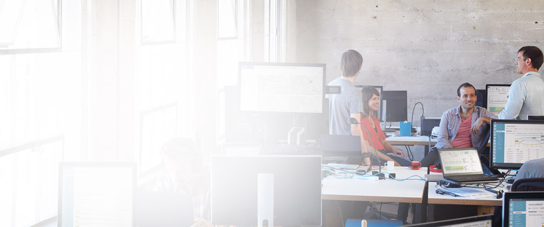 """Penki žmonės, dirbantys biure prie savo stalinių kompiuterių ir naudojantys """"Office 365""""."""