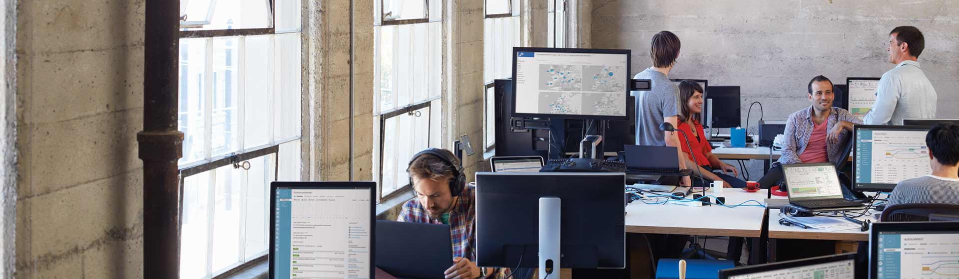 """Grupė bendradarbių, sėdinčių ir stovinčių aplink savo stalus biure, pilname kompiuterių, kuriuose veikia """"Office 365"""""""