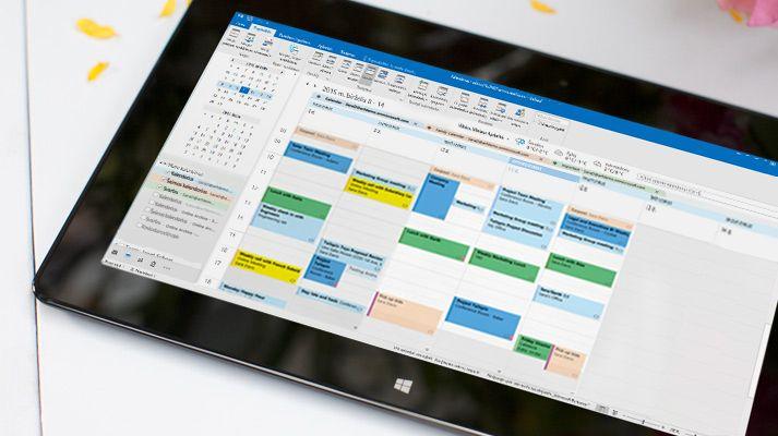 """Planšetinis kompiuteris, kuriame matomas """"Outlook 2016"""" atidarytas kalendorius ir dienos orai."""