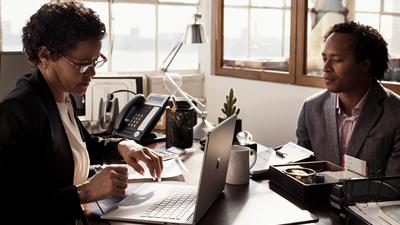 Du žmonės dirba prie stalo, o vienas iš jų turi atvertą nešiojamąjį kompiuterį