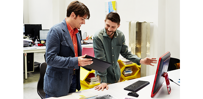 Du vyrai stovi šalia stalo biure ir naudoja planšetinį kompiuterį bendradarbiauti.