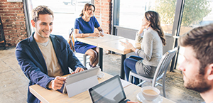 """Du vyrai sėdi prie staliuko kavinėje ir naudoja planšetinius kompiuterius bendradarbiauti. Sužinokite apie """"Microsoft Dynamics CRM""""."""