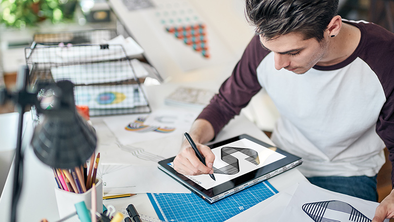 Vyras, sėdintis prie stalo apsuptas grafinio dizaino medžiagos ir konvertuojamojo kompiuterio ekrane piešiantis raidę S