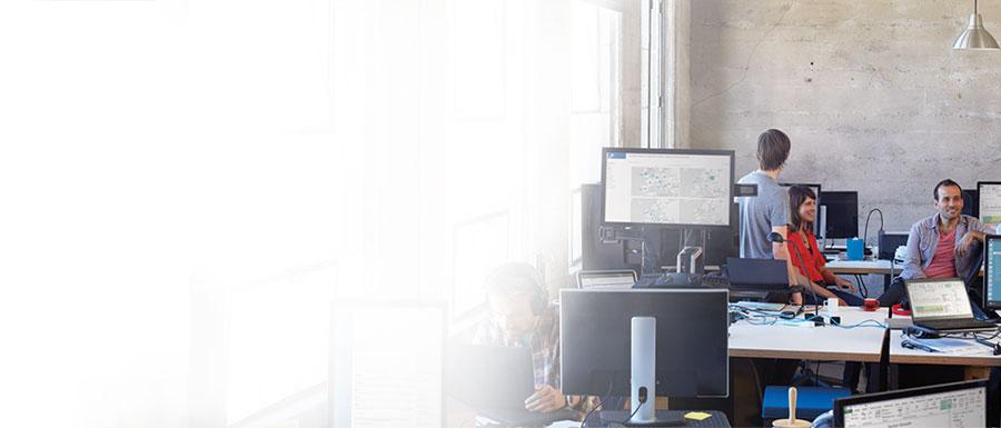 """Keturi žmonės, dirbantys biure prie savo stalinių kompiuterių ir naudojantys """"Office 365""""."""