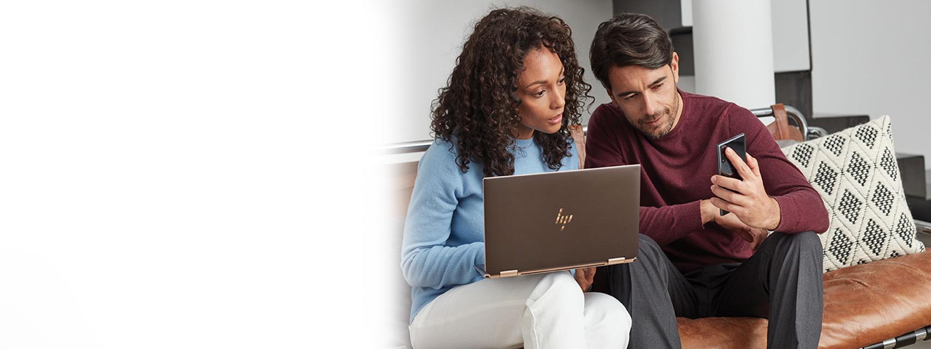 Sieviete un vīrietis sēž uz dīvāna un kopā skatās Windows10 klēpjdatora un mobilās ierīces ekrānos