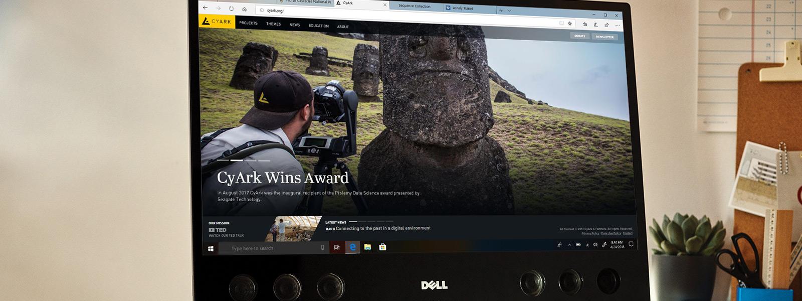 Uz galda novietots datora monitors, kurā redzams Microsoft Edge logs ar 4K Ultra HD izšķirtspējas video
