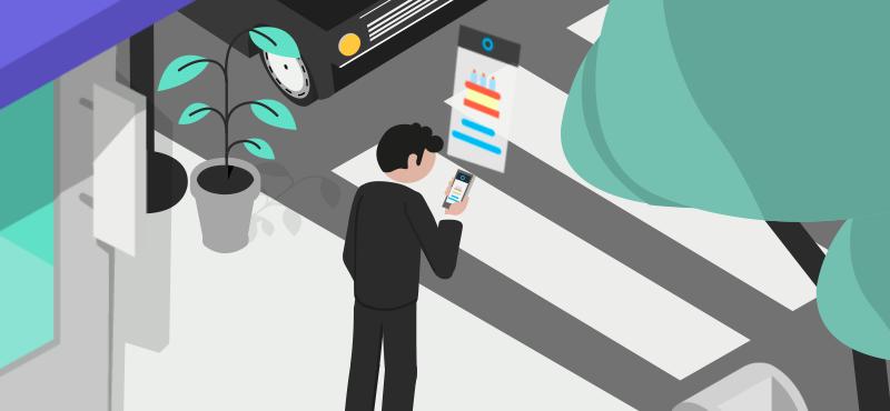 Vīrietis stāv ielas malā un skatās tālrunī