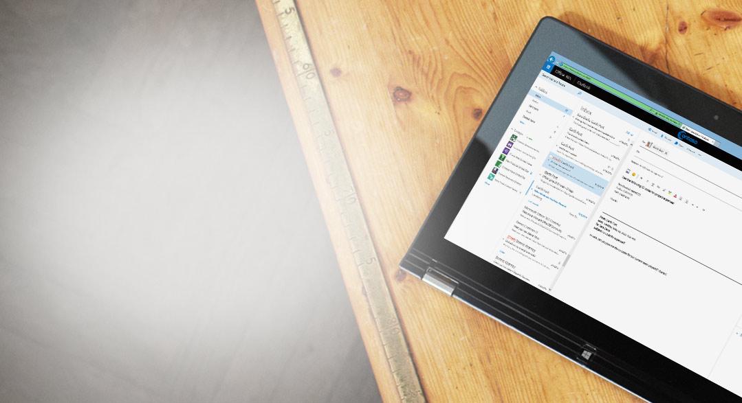 Uz galda atrodas planšetdators, kurā tuvplānā redzams biznesa e-pasta iesūtne, kas darbojas ar Exchange.