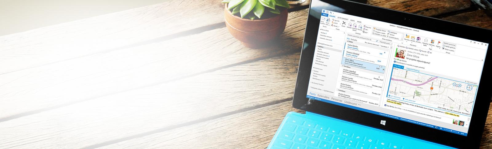Planšetdators, kurā attēlota Microsoft Outlook 2013 iesūtne ar ziņojumu sarakstu un priekšskatījumu.