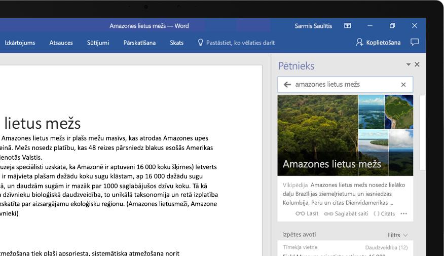 Klēpjdators, kurā redzams Word dokuments un līdzekļa Pētnieks tuvplāns ar rakstu par Amazones lietus mežu