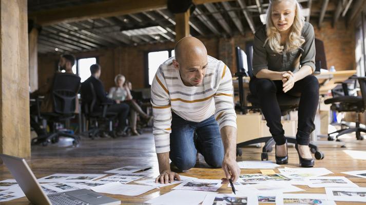 Vīrietis nometies ceļos uz grīdas un rāda uz dokumentiem, kas izklāti uz grīdas, bet sieviete skatās.