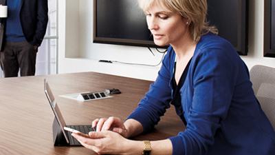 Cilvēks konferenču telpā strādā klēpjdatorā un skatās tālrunī