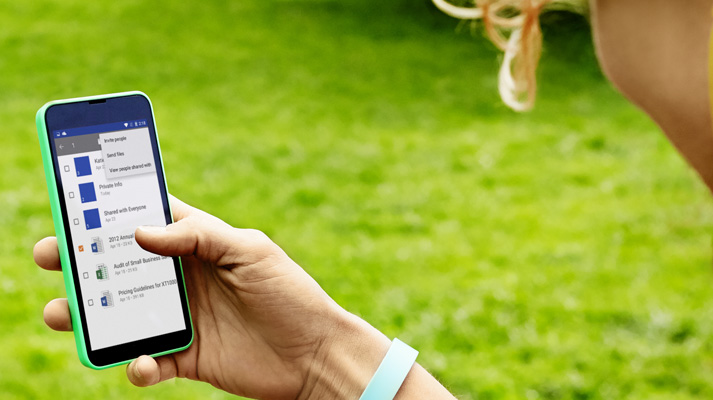 Vienā rokā turēts viedtālrunis, kurā redzams atvērts Office 365.