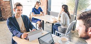 Divi vīrieši sēž pie kafejnīcas galda un sadarbojas, izmantojot planšetdatorus; informācija par Microsoft Dynamics CRM.