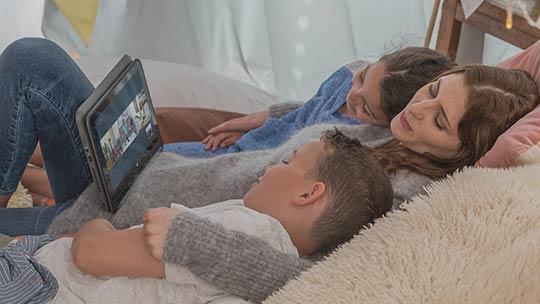 Iepērcieties Microsoft veikalā (attēlā: cilvēki skatās filmu galddatorā)